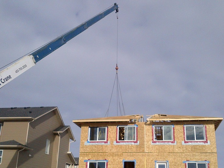 The crane placing the three pieces of the roof onto the house.