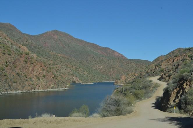 Narrow, winding Apache Trail running along the river.