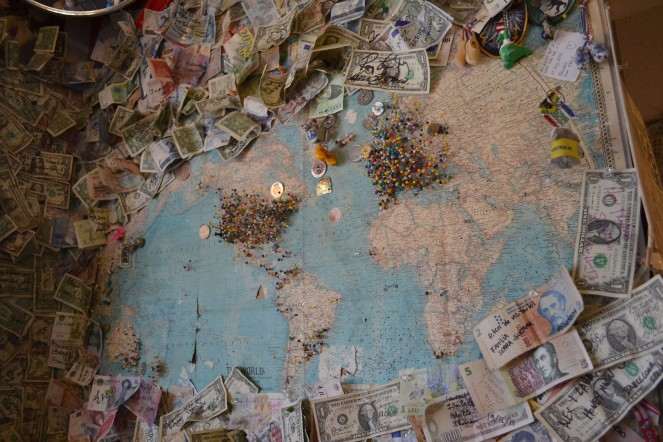 A world map with visitor pins and signed dollar bills in the Hackberry General Store.