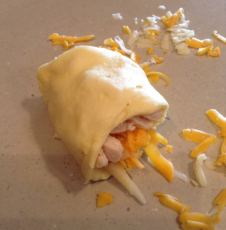 Roll up the chicken and cheese in a crescent roll.