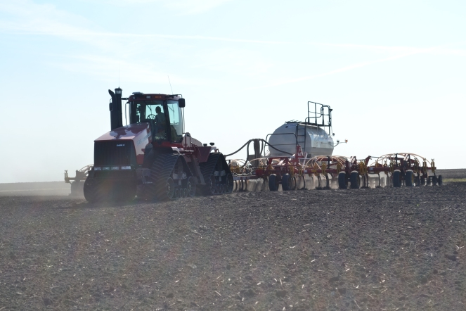 A tractor pulling an air seeder in a field.