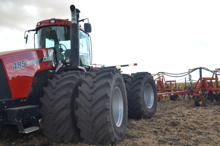A tractor pulling a cultivator in a field.