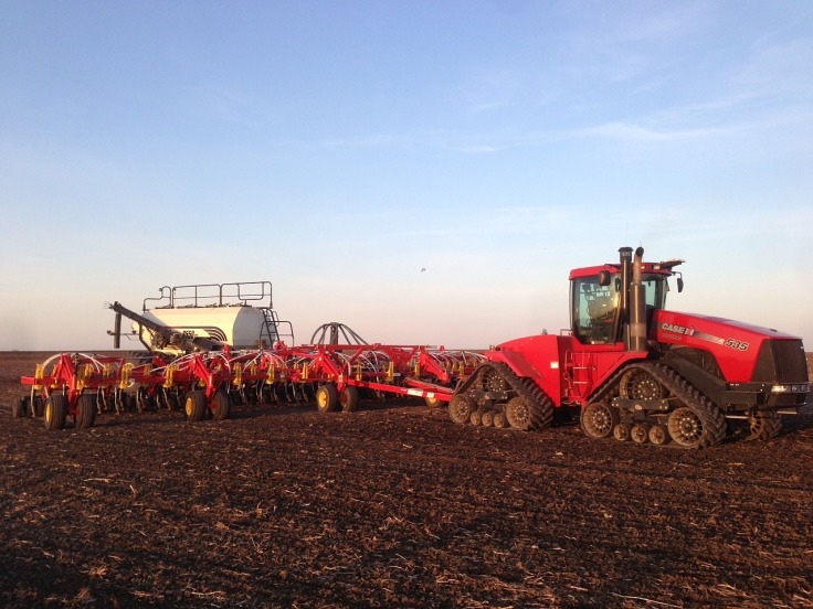 A tractor pulls the air seeder. This unit is used to plant the seeds.